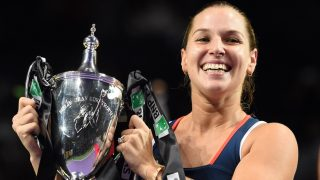 Dominika Cibulkova of Slovakia celebrates with the trophy after victory against Germany's Angelique Kerber at the end of their women's singles final at the WTA Finals tennis tournament in Singapore on October 30, 2016. / AFP PHOTO / ROSLAN RAHMAN