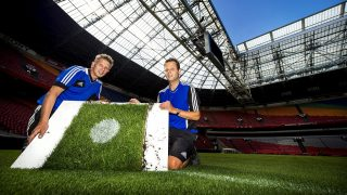 Groundkeepers Jan (L) and Kees Jong poses with the center spot of the Amsterdam Arena Stadium in Amsterdam on August 1, 2013. Ajax Amsterdam is the first Dutch football club with over 250.000 followers on Twitter and celebrates this by raffling the center spot, from the grass on which Ajax won the land championship this year, to one of their followers.. AFP PHOTO / ANP / KOEN VAN WEEL --NETHERLANDS OUT-- / AFP PHOTO / ANP / Koen van Weel