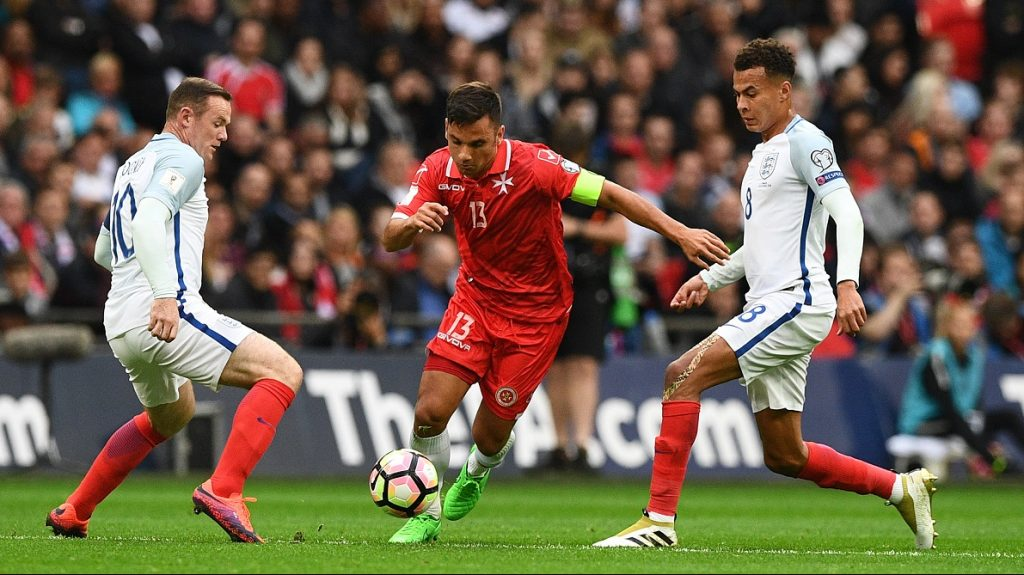 Malta's striker Andre Schembri (C) vies with England's captain Wayne Rooney and England's midfielder Dele Alli (R) during the World Cup 2018 football qualification match between England and Malta at Wembley Stadium in London on October 8, 2016.  / AFP PHOTO / Justin TALLIS / NOT FOR MARKETING OR ADVERTISING USE / RESTRICTED TO EDITORIAL USE