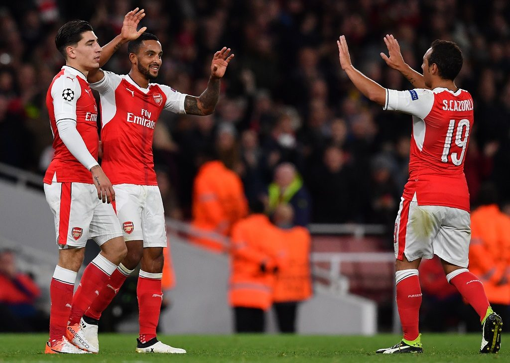 Arsenal's English midfielder Theo Walcott (C) celebrates scoring his team's second goal with Arsenal's Spanish defender Hector Bellerin (L) and Arsenal's Spanish midfielder Santi Cazorla during the UEFA Champions League Group A football match between Arsenal and Ludogorets Razgrad at The Emirates Stadium in London on October 19, 2016. / AFP PHOTO / BEN STANSALL