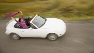 Hispanic women driving convertible car