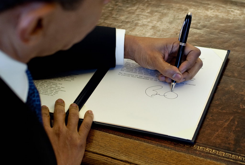 President Barack Obama writes at his desk in the Oval Office 3/3/09. Official White House Photo by Pete Souza