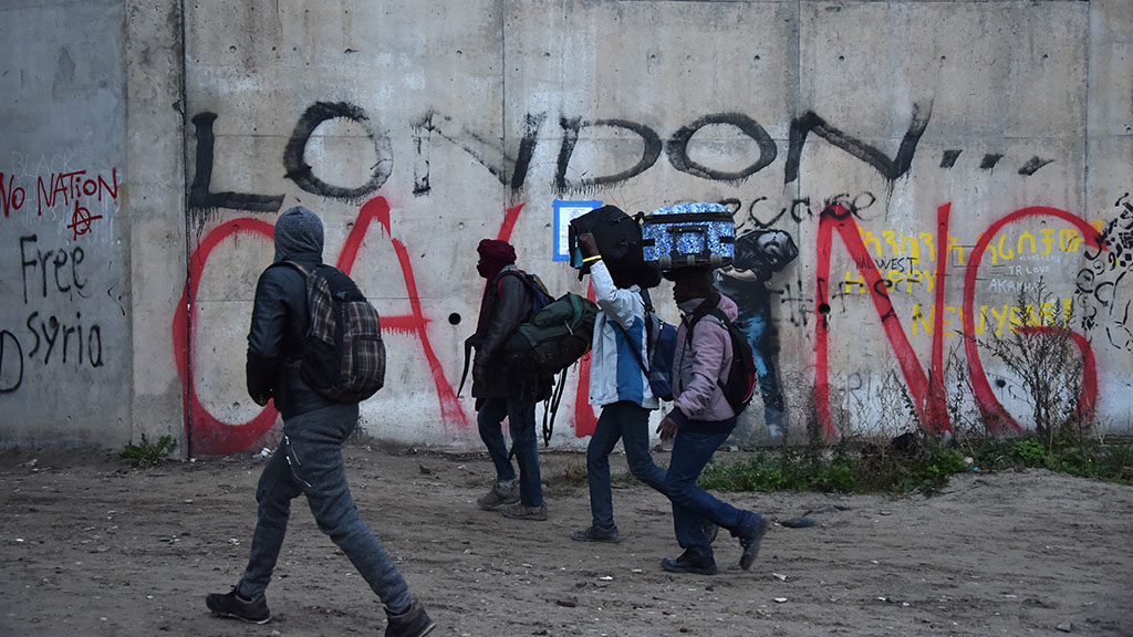 """Migrants with luggage walk past a graffiti on a wall reading """"London calling"""", as they leave the """"Jungle"""" migrant camp, as part of a major three-day operation planned to clear the camp  in Calais, northern France, on October 24, 2016.French authorities are set to begin on October 24, 2016 moving thousands of people out of the notorious Calais Jungle before demolishing the camp that has served as a launchpad for attempts to sneak into Britain. Migrants carrying suitcases and bundles of possessions started queueing up in the early morning darkness at the official meeting points for transportation to reception centres across France. A major three-day operation is planned to clear the sprawling shanty town near Calais port -- a symbol of Europe's failure to resolve its migrant crisis -- of its estimated 6,000-8,000 occupants. / AFP PHOTO / PHILIPPE HUGUEN"""