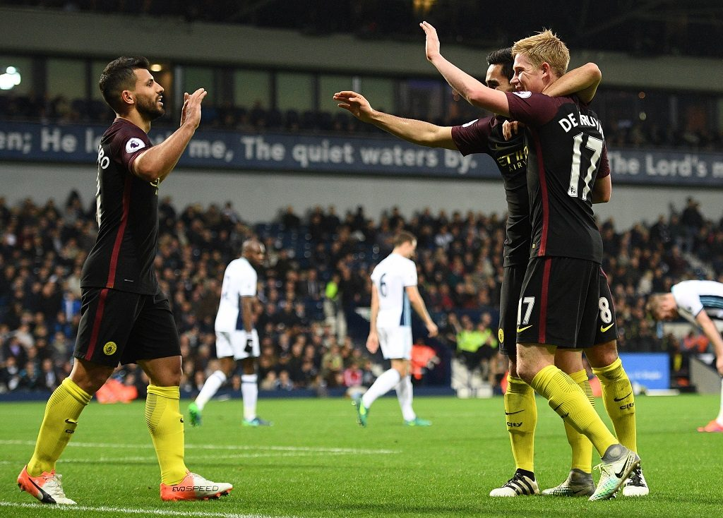 Manchester City's German midfielder Ilkay Gundogan (2nd R) celebrates with Manchester City's Belgian midfielder Kevin De Bruyne and Manchester City's Argentinian striker Sergio Aguero (L) after scoring their fourth goal during the English Premier League football match between West Bromwich Albion and Manchester City at The Hawthorns stadium in West Bromwich, central England, on October 29, 2016. Manchester City won the game 4-0. / AFP PHOTO / Justin TALLIS / RESTRICTED TO EDITORIAL USE. No use with unauthorized audio, video, data, fixture lists, club/league logos or 'live' services. Online in-match use limited to 75 images, no video emulation. No use in betting, games or single club/league/player publications. /