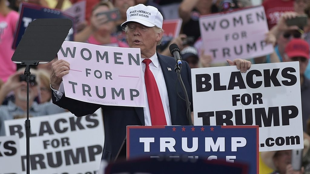 """Republican presidential nominee Donald Trump holds a """"Women for Trump"""" and """"Black for Trump"""" placards during a rally at the Lakeland Linder Regional Airport in Lakeland, Florida on October 12, 2016. / AFP PHOTO / MANDEL NGAN"""