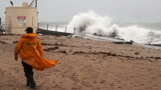 SINGER ISLAND, FL - OCTOBER 06:  A police officer walks along the beach as waves crash ashore as Hurricane Matthew approaches the area on October 6, 2016 in Singer Island, Florida.  The hurricane is expected to make landfall sometime this evening or early in the morning as a possible Category 4 storm.  (Photo by Joe Raedle/Getty Images)