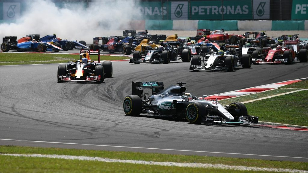 Mercedes AMG Petronas F1 Team's British driver Lewis Hamilton (front) leads start of the race, as Mercedes AMG Petronas F1 Team's German driver Nico Rosberg spins in the pack behind during the Formula One Malaysian Grand Prix in Sepang on October 2, 2016.  / AFP PHOTO / MANAN VATSYAYANA