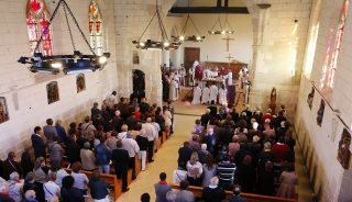 Parishioners attend on October 2, 2016, a special penitential mass to mark the re-opening of the Saint-Etienne-du-Rouvray church and to pay tribute to Father Jacques Hamel, murdered by teenage jihadists, in Saint-Etienne-du-Rouvray, northwestern France. The 85-year-old priest had his throat slit at the foot of the altar on July 26 in an attack claimed by the Islamic State (IS) group. / AFP PHOTO / CHARLY TRIBALLEAU