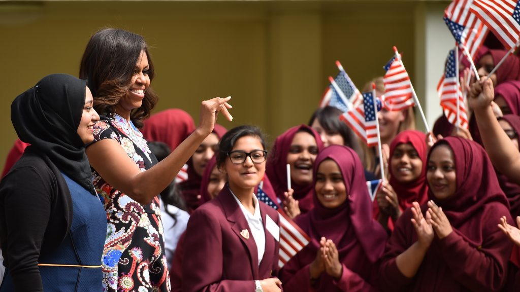 LONDON, ENGLAND - JUNE 16:  Young women wave the American flag as they greet US First Lady Michelle Obama in the courtyard before an event as part of the 'Let Girls Learn Initiative' at the Mulberry School for Girls on June 16, 2015 in London, England. The US First Lady is travelling with her daughters, Malia and Sasha and her mother, Mrs. Marian Robinson, to continue a global tour promoting her 'Let Girls Learn Initiative'. The event at the school was to discuss how the UK and USA are working together to expand girl's education around the world.  (Photo by Jeff J Mitchell/Getty Images)