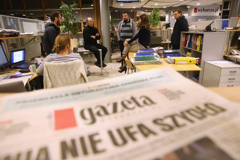 """WARSAW, POLAND - FEBRUARY 26:  Piotr Stasinski (C-L, in black), Deputy Editor-in-Chief of Polish independent daily newspaper Gazeta Wyborcza, speaks with editorial colleagues in the newsroom of the paper near a copy of Gazeta Wyborcza whose headline reads: """"The EU Distrusts Szydlo"""", in reference to new Polish Prime Minister Beata Szydlo, on February 26, 2016 in Warsaw, Poland. Independent media in Poland currently face a new, uncertain political atmosphere with the conservative and populist Law and Justice (PiS) political party, led by Jaroslaw Kaczynski, having won elections last year and appointing President Andrzej Duda and Prime Minister Beata Szydlo. Since taking office PiS legislators have curtailed the power of the Constitutional Court and removed critical journalists from state-owned media. Stasinski says critics charge Gazeta Wyborcza is too anti-PiS and hence too partisan, though he says the paper's strident role is crucial in defending democracy in Poland under the new government.  (Photo by Sean Gallup/Getty Images)"""