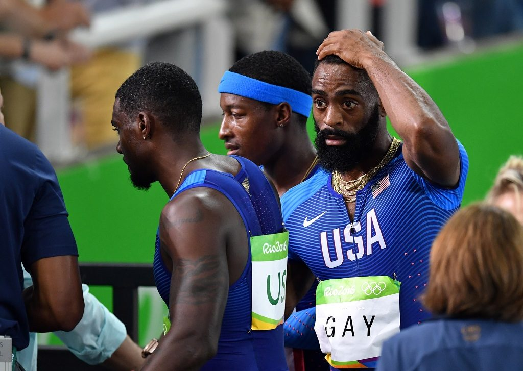 USA's Tyson Gay (C) reacts after his team's disqualification from the Men's 4x100m Relay Final during the athletics event at the Rio 2016 Olympic Games at the Olympic Stadium in Rio de Janeiro on August 19, 2016.   / AFP PHOTO / PEDRO UGARTE