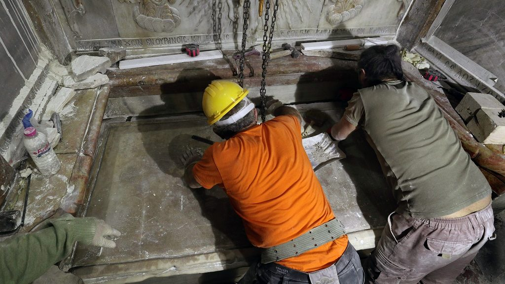 Greek preservation experts place back the marble slab stone that covered the Tomb of Jesus, where his body is believed to have been laid, after it was removed for 3 days to allow the team to do restoration works and study as part of conservation work done by the Greek team in Jerusalem on late on October 28, 2016. The experts from the National Technical University of Athens for cultural heritage preservation removed the marble slab stone that covered the original tomb since the last restoration of the edicule on 1810 by Greek architect Nikolaos Komnenos. The Church of the Holy Sepulchre in Jerusalem's Old City is traditionally believed to be the site of Jesus's burial and attracts every year millions of pilgrims from all over the world.  / AFP PHOTO / GALI TIBBON