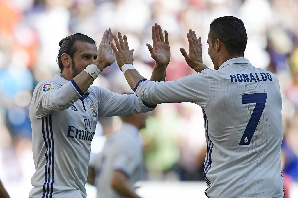 Real Madrid's Welsh forward Gareth Bale (L) and Real Madrid's Portuguese forward Cristiano Ronaldo celebrate after scoring a goal during the Spanish league football match Real Madrid CF vs SD Eibar at the Santiago Bernabeu stadium in Madrid on October 2, 2016. / AFP PHOTO / JAVIER SORIANO