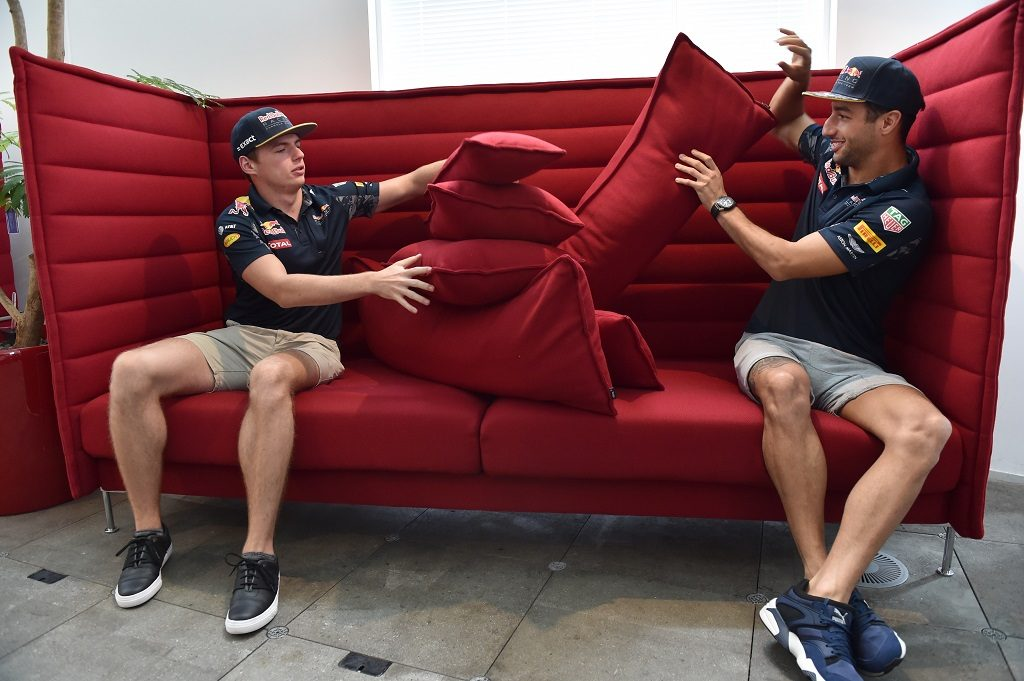 """Red Bull Racing's Australian driver Daniel Ricciardo (R) and Belgian-Dutch driver Max Verstappen (L) pile up pillows on a sofa during a photo session for the media in Tokyo on October 5, 2016, ahead of the Japanese Grand Prix.  Still buzzing from his Malaysia win, Red Bull Racing's Australian driver Daniel Ricciardo has promised to """"kick ass"""" in Japan this weekend -- and that could be bad news for Nico Rosberg. / AFP PHOTO / KAZUHIRO NOGI"""