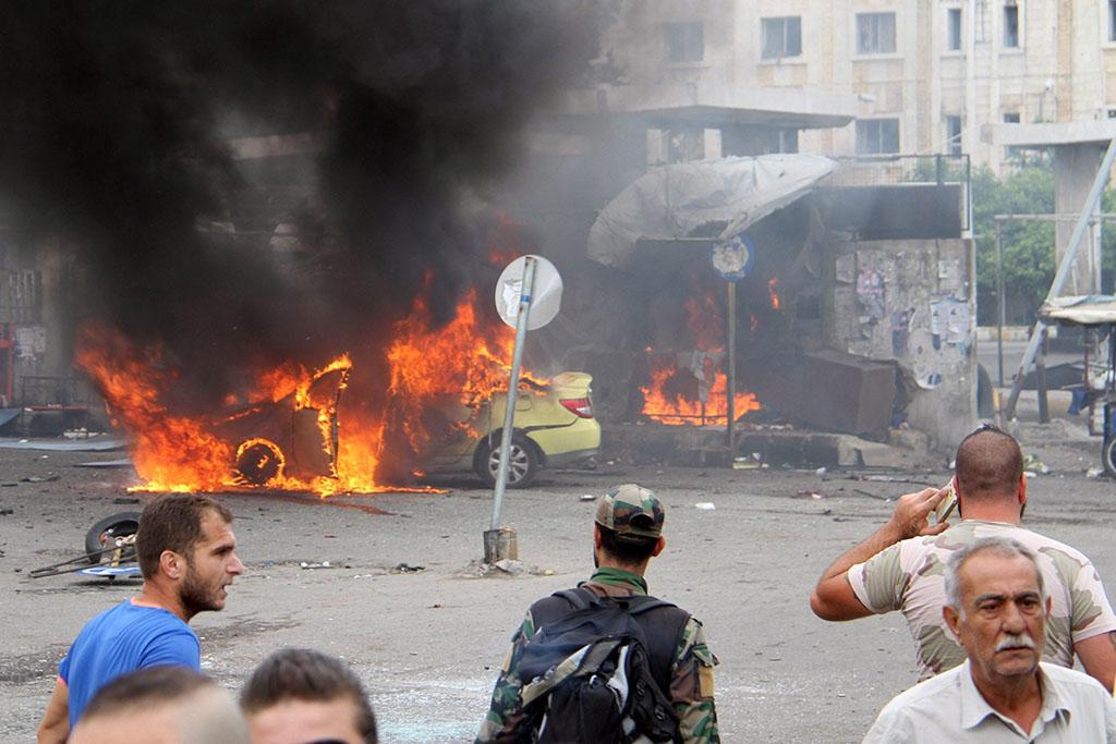 Tartúsz, 2016. május 23. A SANA szíriai állami hírügynökség által közreadott kép egy autóba rejtett pokolgépes merénylet helyszínéről az északnyugat-szíriai Tartúszban 2016. május 23-án. Ezen a napon az Iszlám Állam dzsihadista terrorszervezet összesen hét gépjárműbe rejtett pokolgépet hozott működésbe közel azonos időben a Földközi-tenger partja menti városokban. Tartúszban legalább 48, míg a mintegy hatvan kilométerre északra fekvő Dzsablában 53 ember vesztette életét a robbantásokban. (MTI/EPA/SANA)