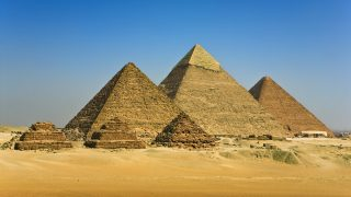 """Egypt. Cairo - Giza. General view of pyramids from the Giza Plateau (there is three pyramids popularly known as Queens' Pyramids on front side; next in order from left - the Pyramid of Menkaure /Mykerinos/, Khafre /Chephren/ and Chufu /Cheops/ - known as the Great Pyramid). The Pyramid Fields from Giza to Dahshur is on UNESCO World Heritage List"""