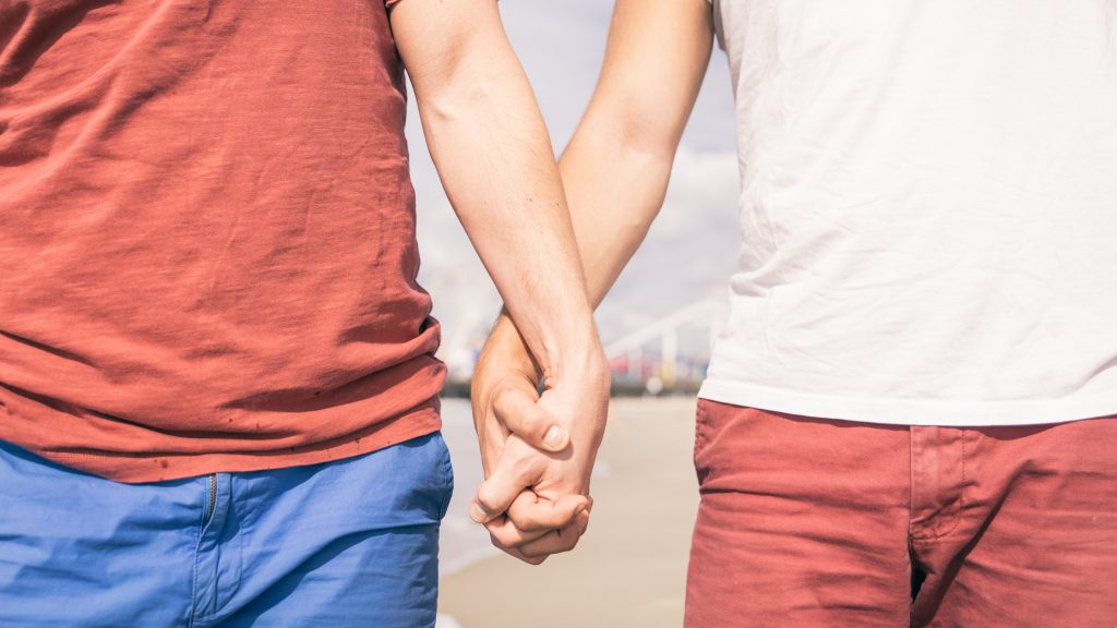 Gay couple walking on the beach. concept about homosexuality