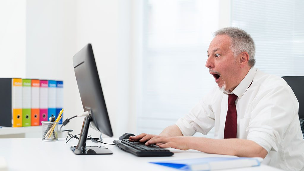 Amazed businessman in front of his computer