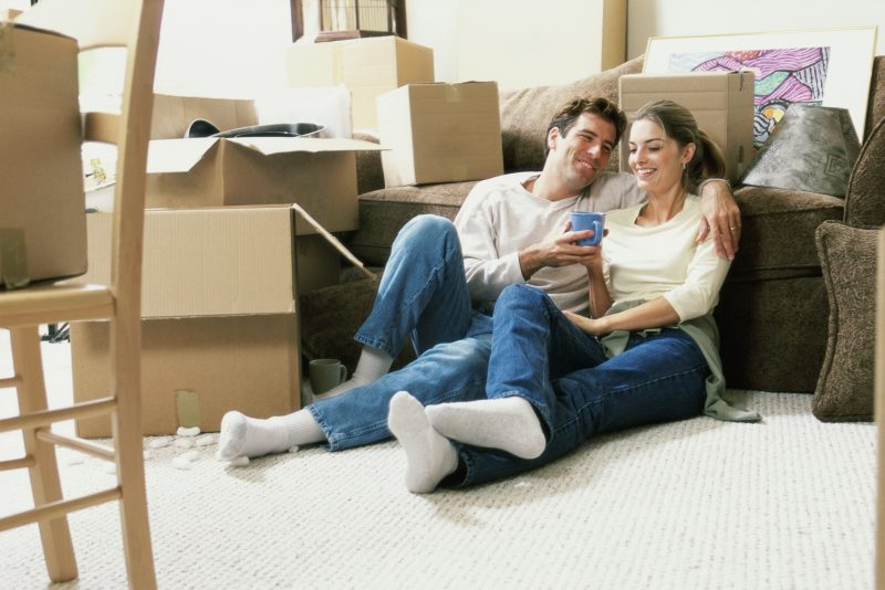 Young couple holding a coffee cup sitting on the floor