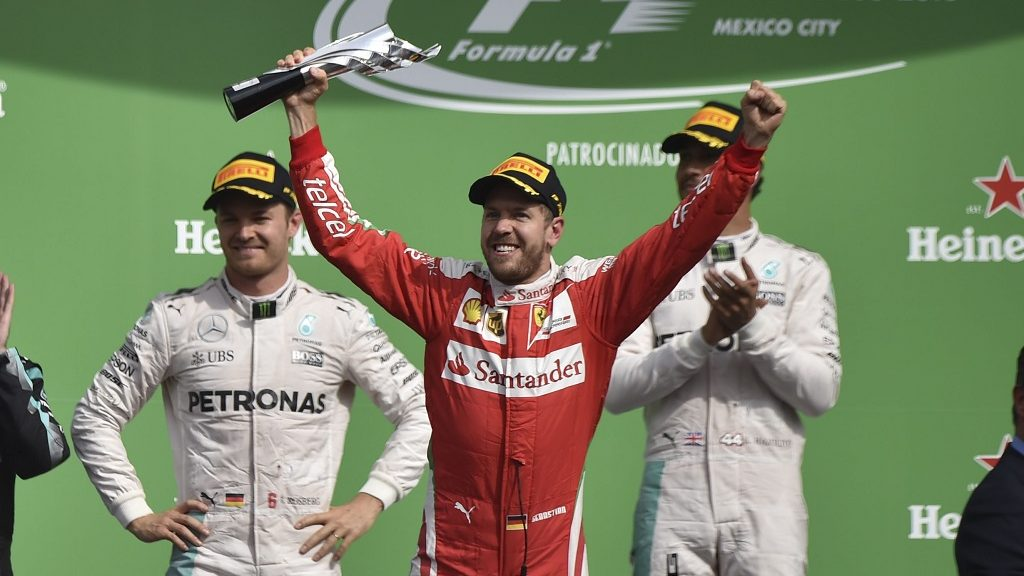 (FILES) This file photo taken on October 30, 2016 shows Scuderia Ferrari's German driver Sebastian Vettel (C) celebrating his third place in the podium next to Mercedes AMG Petronas F1 Team British driver Lewis Hamilton (R) and German driver Nico Rosberg (L) at the end of the Formula One Mexico Grand Prix, at the Hermanos Rodriguez circuit in Mexico City. Ferrari driver Sebastian Vettel was penalized 10 points and dropped to fifth place, race officials said. The move promotes Australian Red Bull driver Daniel Ricciardo to third place and his teammate Max Verstappen of the Nethlerlands to fourth in the final standings of the race won by Lewis Hamilton ahead of his Mercedes team-mate Nico Rosberg.  / AFP PHOTO / YURI CORTEZ
