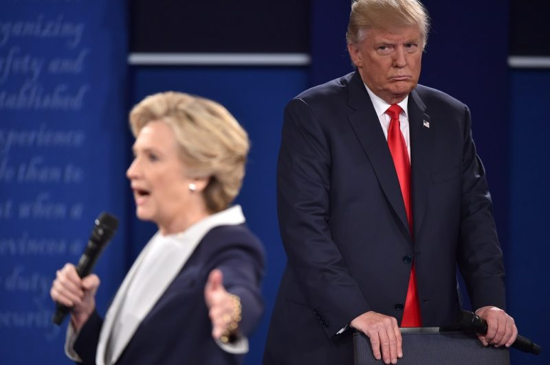 Republican presidential candidate Donald Trump listens to Democratic presidential candidate Hillary Clinton during the second presidential debate at Washington University in St. Louis, Missouri on October 9, 2016. / AFP PHOTO / Paul J. Richards