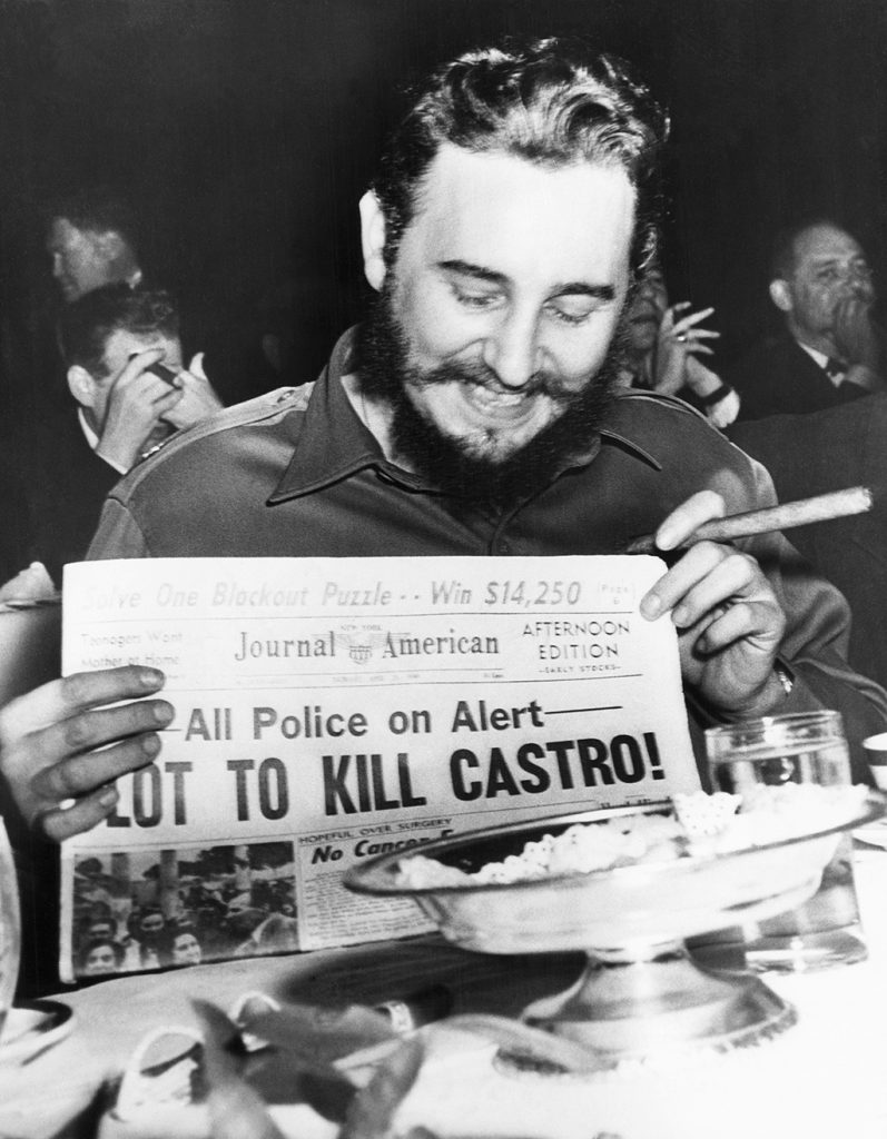 "(Original Caption) Seems amused by assassination plot...Seeming quite amused, Cuban Prime Minister Fidel Castro holds up a newspaper headlining the discovery of a plot to kill Castro here, April 23rd. Castro was at the Overseas Press Club at the time. Police said five brothers had been sent here from Philadelphia, Pa., to assassinate the bearded leader. Police said that three other men, including a sixth brother, were believed to be in New York in connection with the plot to kill Castro. Earlier in the day, when asked about a reported assassination attempt, Castro had replied, ""In Cuba, they had tanks, planes and they run away. So what are they going to do here? I sleep well and don't worry at all."""