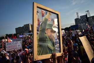 Cubans display a pictures of Cuban former president Fidel Castro during the May Day parade in Havana, on May 1, 2016. / AFP PHOTO / ADALBERTO ROQUE