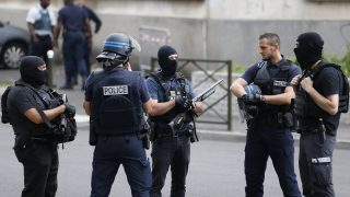 """French police officers and anti-crime brigade stand guard during an anti-terrorist operation on July 21, 2016 in Argenteuil, northwestern suburbs of Paris. """"Searches are being conducted in two locations by French intelligence agency (DGSI) and French Police unit (Raid)"""", according to police. / AFP PHOTO / MATTHIEU ALEXANDRE"""