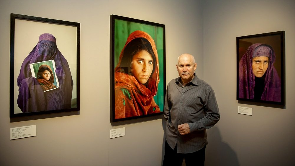 """US photographer Steve McCurry poses next to his photos of the """"Afghan Girl"""" named Sharbat Gula at the opening of the """"Overwhelmed by Life"""" exhibition of his work at the Museum for Art and Trade in Hamburg, northern Germany on June 27, 2013. The exhibition comprises some 120 photographs taken between 1980 and 2012 in countries such as Afghanistan, the United States, Pakistan, India, Tibet, Kashmir, Cambodia, Indonesia, Burma and Kuwait.  AFP PHOTO / DPA / ULRICH PERREY   GERMANY OUT  RESTRICTED TO EDITORIAL USE, MANDATORY MENTION OF THE ARTIST UPON PUBLICATION, TO ILLUSTRATE THE EVENT AS SPECIFIED IN THE CAPTION / AFP PHOTO / DPA / ULRICH PERREY"""