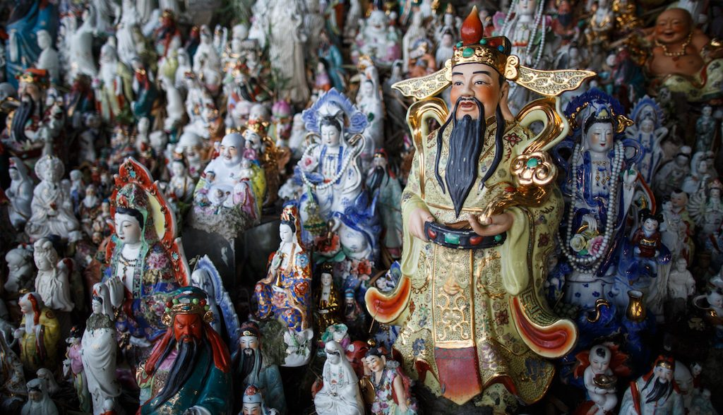 """This picture taken on August 9, 2016 shows a display of unwanted statues of deities, gathered and repaired after their owners discarded them, on a rocky slope running down to the sea in Hong Kong.  Religion and local customs permeate Hong Kong, where Buddhist and Taoist temples are common and incense offerings are regularly burned outside local businesses. Private homes often have a shrine to a local deity, with Christian churches and mosques also in the mix. But with space at a premium in a city were rents are sky high, informal collections of discarded gods often decorate roadsides and public spaces. / AFP PHOTO / Anthony WALLACE / To go with """"HONG KONG-CULTURE-LIFESTYLE-RELIGION"""", FEATURE by Dennis Chong"""