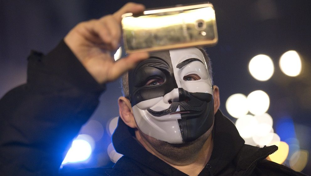 """A masked protester uses a smartphone during the anti-capitalist 'Million Masks March', organised by the group Anonymous, in London on November 5, 2016 to protest austerity, government policy and what they consider corperate greed.  Activists gathered for a march on the night of Britain's Guy Fawkes Night with many wearing white masks of the man who was caught plotting to blow up parliament in 1605, now associated with the group Anonymous. Police made dozens of arrests during the protest on suspicion of various offences.  / AFP PHOTO / Justin TALLIS / """"The erroneous mention[s] appearing in the metadata of this photo has been modified in AFP systems in the following manner: [BYLINE IS JUSTIN TALLIS] instead of [NIKLAS HALLE'N]. Please immediately remove the erroneous mention[s] from all your online services and delete it (them) from your servers. If you have been authorized by AFP to distribute it (them) to third parties, please ensure that the same actions are carried out by them. Failure to promptly comply with these instructions will entail liability on your part for any continued or post notification usage. Therefore we thank you very much for all your attention and prompt action. We are sorry for the inconvenience this notification may cause and remain at your disposal for any further information you may require."""""""