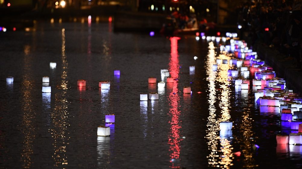 """People set afloat lanterns during a lantern ceremony given by the association """"ToujoursParis.fr"""" at the Canal Saint-Martin in Paris on November 13, 2016 to mark the first anniversary of the Paris terror attacks.   130 people were killed on November 13, 2015 by gunmen and suicide bombers from the Islamic State (IS) group in a series of coordinated attacks in and around Paris.  / AFP PHOTO / Martin BUREAU"""
