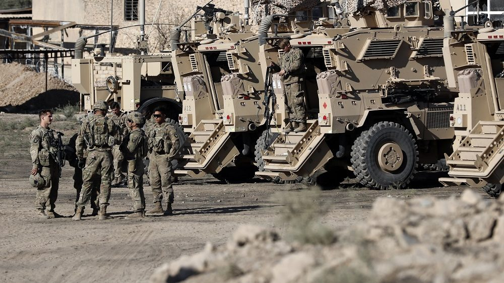 US soldiers are seen next to their armoured vehicles near an Iraqi army base on the outskirts of Mosul, on November 23, 2016.     Forces battling the Islamic State group in northern Iraq cut off the jihadists' last supply line from Mosul to Syria, trapping them in the city for a bloody last stand.    / AFP PHOTO / THOMAS COEX