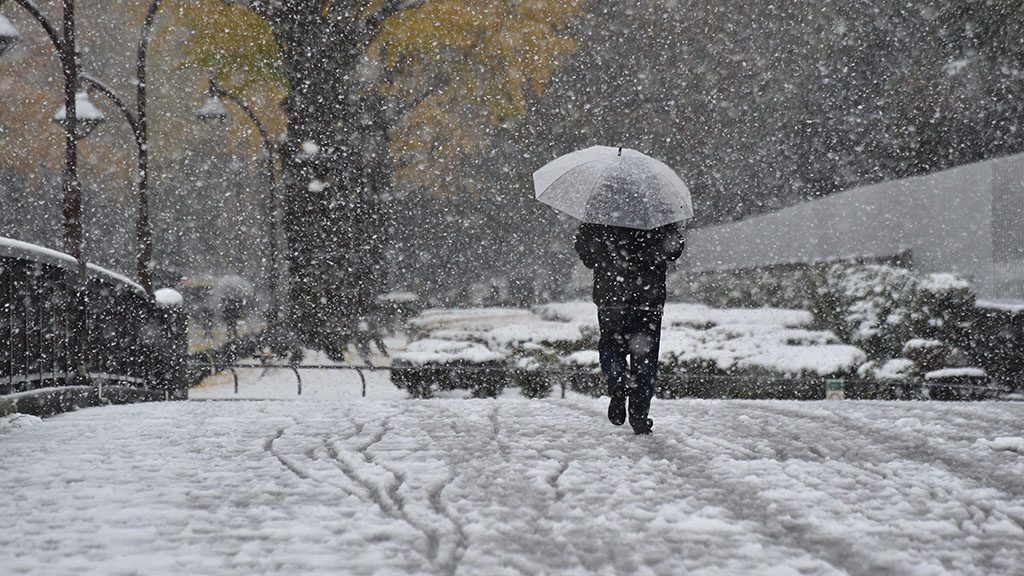 A pedestrian walks in snowfall in Tokyo on November 24, 2016. 