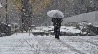 A pedestrian walks in snowfall in Tokyo on November 24, 2016. Tokyo woke up on November 24 to its first November snowfall in more than half a century, leaving commuters to grapple with train disruptions and slick streets. / AFP PHOTO / Kazuhiro NOGI