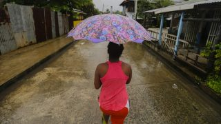 """A woman walks along the street at """"El Canal"""" neighbourhood before Hurricane Otto hits Bluefields, Nicaragua on November 24, 2016. A powerful hurricane churned toward Nicaragua and Costa Rica with freight-train winds and heavy rains expected to trigger dangerous floods and mudslides. / AFP PHOTO / INTI OCON"""