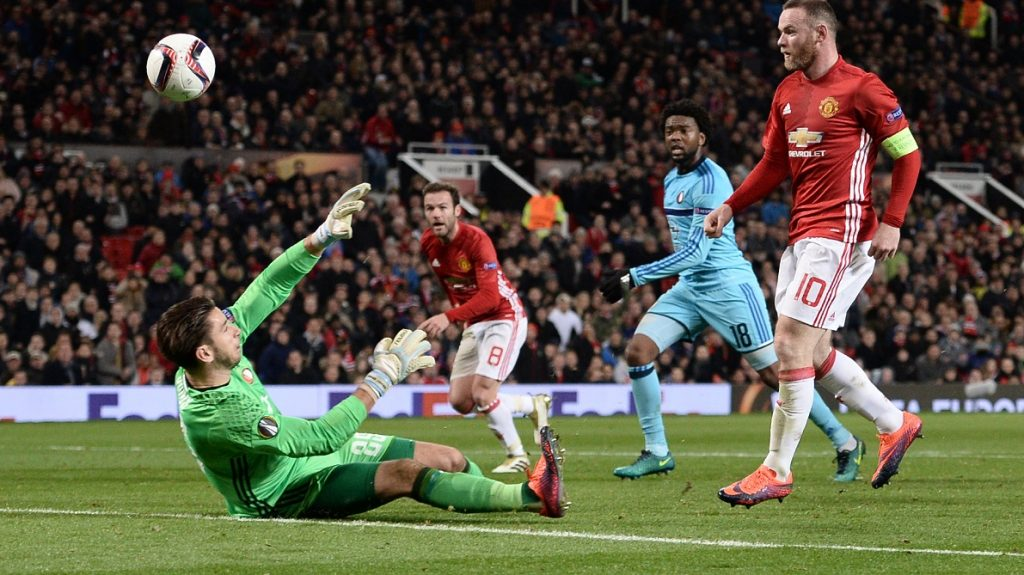 Manchester United's English striker Wayne Rooney (R) chips the ball over Feyenoord's Australian goalkeeper Brad Jones (L) to score the opening goal during the UEFA Europa League group A football match between Manchester United and Feyenoord at Old Trafford stadium in Manchester, north-west England, on November 24, 2016. / AFP PHOTO / Oli SCARFF