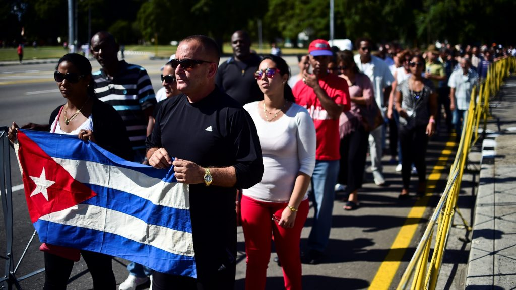 People holding a Cuban national flag queue to enter Jose Marti's memorial to pay their last respects to Cuban revolutionary icon Fidel Castro at Revolution Square in Havana, on November 28, 2016.  A titan of the 20th century who beat the odds to endure into the 21st, Castro died late Friday after surviving 11 US administrations and hundreds of assassination attempts. No cause of death was given. Castro's ashes will go on a four-day island-wide procession starting Wednesday before being buried in the southeastern city of Santiago de Cuba on December 4. / AFP PHOTO / RONALDO SCHEMIDT