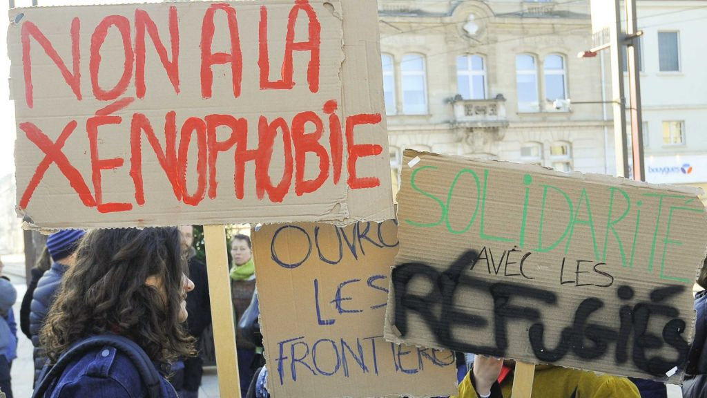 FRANCE, Le Mans: Protesters hold signs reading ' No to xenophobia' and 'solidarity with refugees' during a rally for refugees in Le Mans on October 22, 2016. - Francois NAVARRO