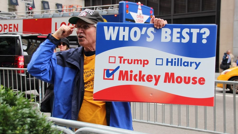 A demonstrator stands with a poster written with Who's best? Trump. Hillary. Mickey Mouse.' outside of Trump Tower in Manhattan, New York, USA, 28 October 2016. Photo:CHRISTINAHORSTEN/dpa