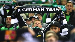 """MOENCHENGLADBACH, GERMANY - NOVEMBER 01:  A Borussia Moenchengladbach fan holds up a scarf reading 'A German team' prior to kick off during the UEFA Champions League Group C match between VfL Borussia Moenchengladbach and Celtic at Borussia-Park on November 1, 2016 in Moenchengladbach, Germany. A sign outside a Scottish bar went viral before the club's 2-0 Champions League win over Celtic, after the author seemingly gave up attempting to spell """"Moenchengladbach"""" - instead opting for """"A German Team"""". (Photo by Alex Grimm/Bongarts/Getty Images)"""