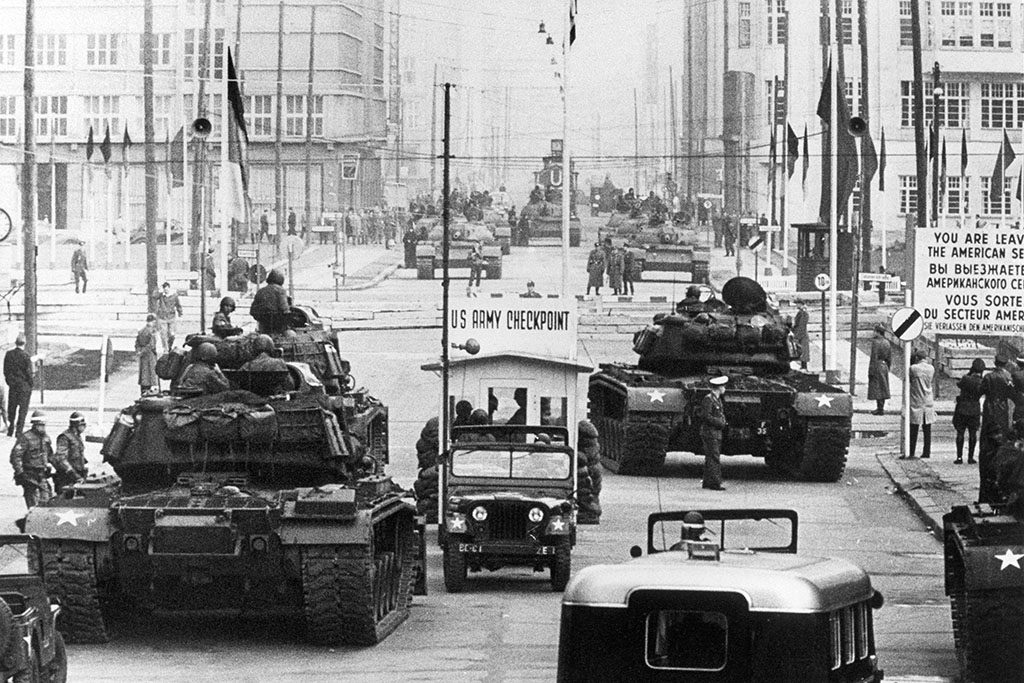 Allied and Soviet tanks face each other , in October 1961, across the famous border of the American sector in Berlin, at Checkpoint Charlie crossing point, the only one in the Berlin Wall between East (Soviet sector, background) and West Berlin (American sector) used only by diplomats and foreigners. The Berlin wall built by the East German government to seal off East Berlin from the part of the city occupied by the three main western powers (USA, Great Britain and France), and to prevent mass illegal emigration to the West. The wall, built along the border between German Democratic Republic (GDR) and Federal Republic of Germany, was the scene of the shooting of many East Germans who tried to escape from GDR. The two countries remained divided until November 1989 when the wall was unexpectedly opened following increased pressure for political reform in GDR.