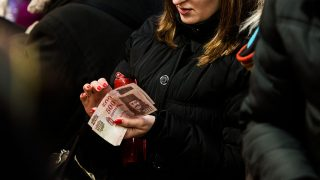 A shopper counts 500 Hungarian forint banknotes at the Christmas market in Vorosmarty square in Budapest, Hungary, on Saturday, Dec. 5, 2015. Hungary GDP growth slowed less than forecast to 2.4% year on year in the third quarter. Photographer: Akos Stiller/Bloomberg via Getty Images