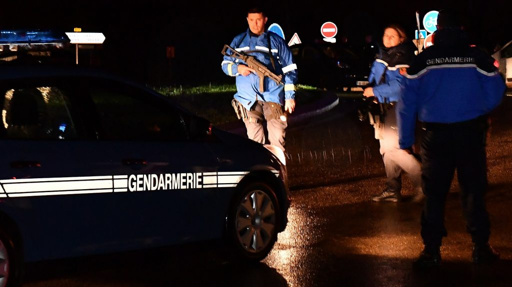 """Gendarmes stand guard on a road near a retirement home for monks in Montferrier-sur-Lez, southern France, early on November 25, 2016, after an armed man burst in the home killing a woman with a knife. Armed police were hunting the man inside the home, which is home to around 70 men and women who have served as missionaries in Africa. Authorities said it was a """"criminal act"""". / AFP PHOTO / PASCAL GUYOT"""