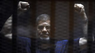 CAIRO, EGYPT - JUNE 02: Former Egyptian President Mohamed Morsi gestures as he stands inside the defendants' cage in a courtroom during his trial in Cairo, Egypt, on June 02, 2015. An Egyptian court postponed Tuesday the verdict in former President Mohamed Morsi's jailbreak and espionage cases to June 16.  Last month, the court had asked for the opinion of Egypts highest religious authority on death sentences it issued against Morsi and 105 co-defendants who were accused of taking part in a mass jailbreak during Egypt's 2011 uprising that ousted former President Hosni Mubarak. (Photo by Mohamed Mahmoud/Anadolu Agency/Getty Images)