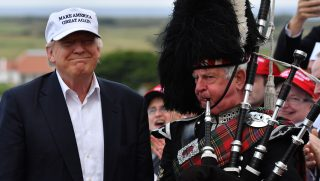 AYR, SCOTLAND - JUNE 24:  A bagpipe player wears traditional dress next to Presumptive Republican nominee for US president Donald Trump as he arrives to his Trump Turnberry Resort on June 24, 2016 in Ayr, Scotland. Mr Trump arrived to officially open his golf resort which has undergone an eight month refurbishment as part of an investment thought to be worth in the region of two hundred million pounds.  (Photo by Jeff J Mitchell/Getty Images)