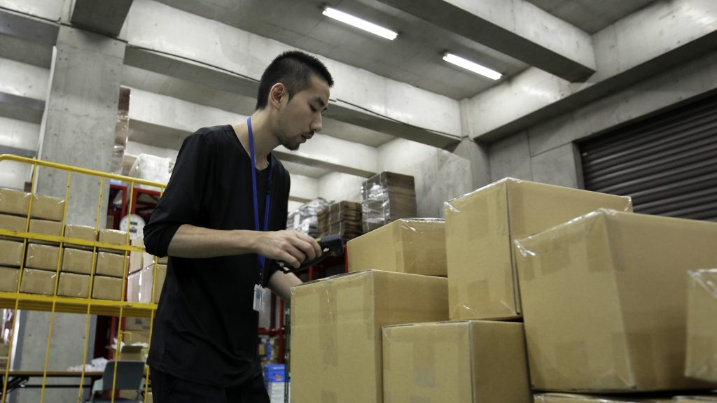 An employee scans parcels for distribution at a warehouse for Inagora Inc.'s Wandou cross-border e-commerce service application in Tokyo, Japan, on Tuesday, July 26, 2016. Thanks to Wandou, one of the most downloaded shopping apps in China in June, and other businesses facilitating cross-border sales, Chinese consumers are set to create what Japans Ministry of Economy, Trade and Industry predicts will become a 2.34 trillion yen e-commerce market by 2019. Photographer: Kiyoshi Ota/Bloomberg via Getty Images