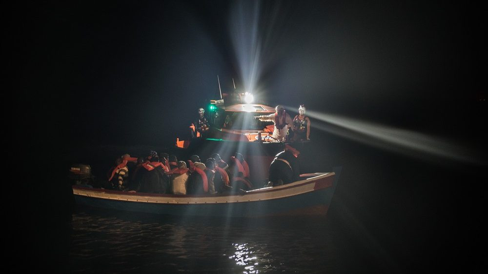 POZZOLLO, ITALY - NOVEMBER 22:  Refugees are escorted to the Topaz Responder in a wooden boat as members of MOAS, Migrant Offshore Aid Station make rescues at sea on November 22, 2016 in Pozzollo Italy. The MOAS team worked through the night and into the next morning rescuing 'approximately' 600 people from vessels. MOAS are currently patrolling international waters off the coast of Libya, and running rescue missions for the many migrants and refugees who continue to attempt to make the dangerous crossing across the Mediterranean Sea to Italy. MOAS are a Malta based registered foundation dedicated to providing professional search-and-rescue assistance to refugees and migrants in distress at sea and work alongside with the Red Cross on board the Topaz Responder. The number of deaths this year of people crossing the Mediterranean has risen to almost 4,300. MOAS alone have rescued around 19,000.  (Photo by Dan Kitwood/Getty Images)