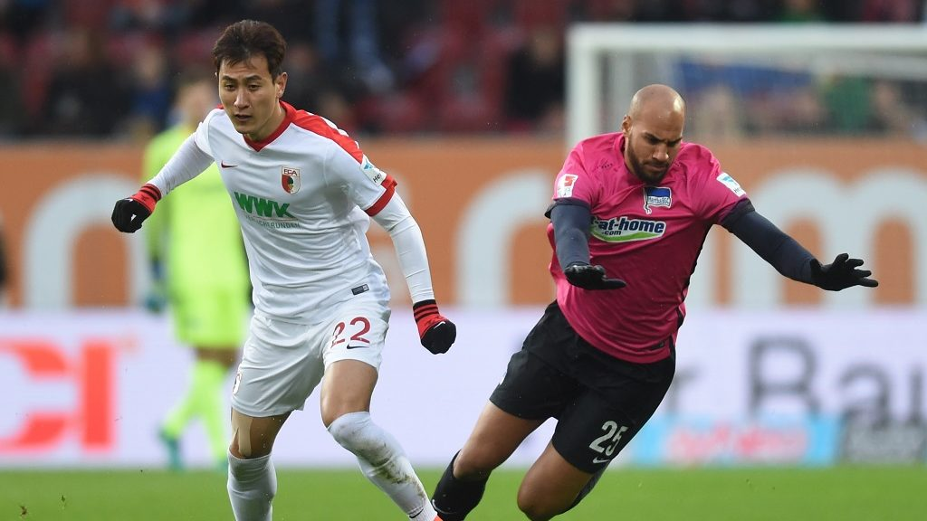 Augsburg's Korean midfielder Dong-Won Ji (L) and Berlin's US defender John Anthony Brooks vie for the ball during the German First division Bundesliga football match FC Augsburg vs Hertha Berlin, in Augsburg, southern Germany, on November 19, 2016. / AFP PHOTO / CHRISTOF STACHE / RESTRICTIONS: DURING MATCH TIME: DFL RULES TO LIMIT THE ONLINE USAGE TO 15 PICTURES PER MATCH AND FORBID IMAGE SEQUENCES TO SIMULATE VIDEO. == RESTRICTED TO EDITORIAL USE == FOR FURTHER QUERIES PLEASE CONTACT DFL DIRECTLY AT + 49 69 650050