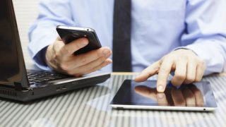 businessman is working on tablet and using smart phone